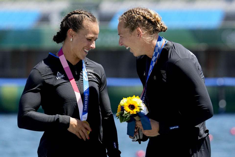 Lisa Carrington, left, and Caitlin Regal, of New Zealand, celebrate their gold medals after winning the women's kayak double 500m final at the 2020 Summer Olympics, Tuesday, Aug. 3, 2021, in Tokyo, Japan. (AP Photo/Lee Jin-man)