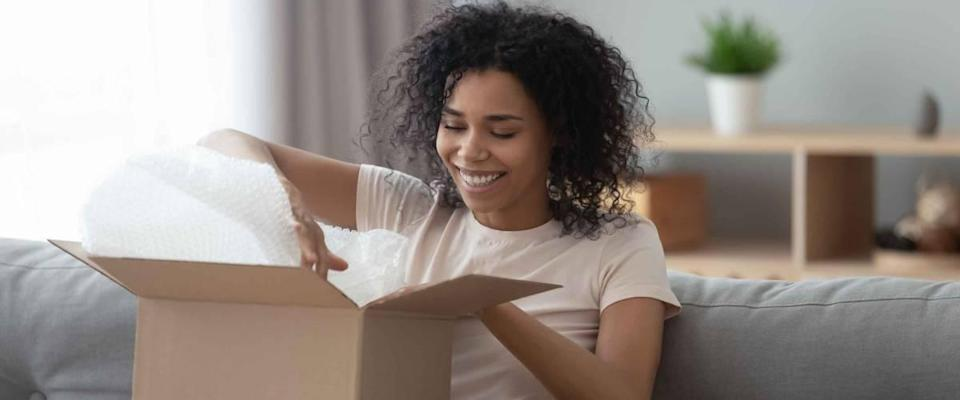 Happy young african woman satisfied customer open parcel cardboard box sit on sofa at home
