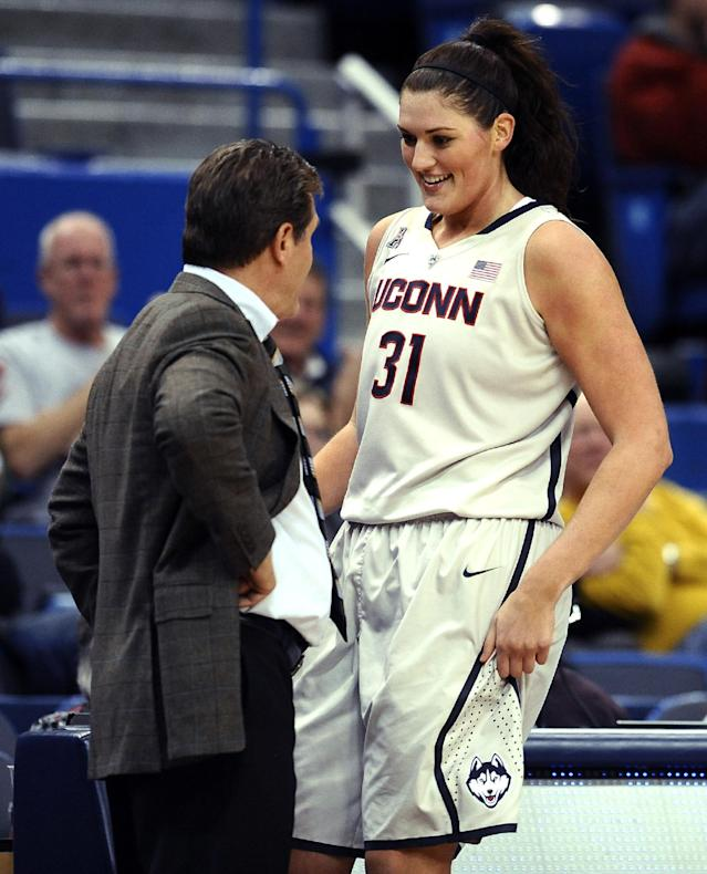 Connecticut's Stefanie Dolson, right, is greeted by Connecticut head coach Geno Auriemma after finishing play during the second half of an NCAA college basketball game against Oregon with a triple-double, Wednesday, Nov. 20, 2013, in Hartford, Conn. Dolson left the game with 26 points, 14 rebounds and 11 assists for the second triple-double in UConn's history. (AP Photo/Jessica Hill)