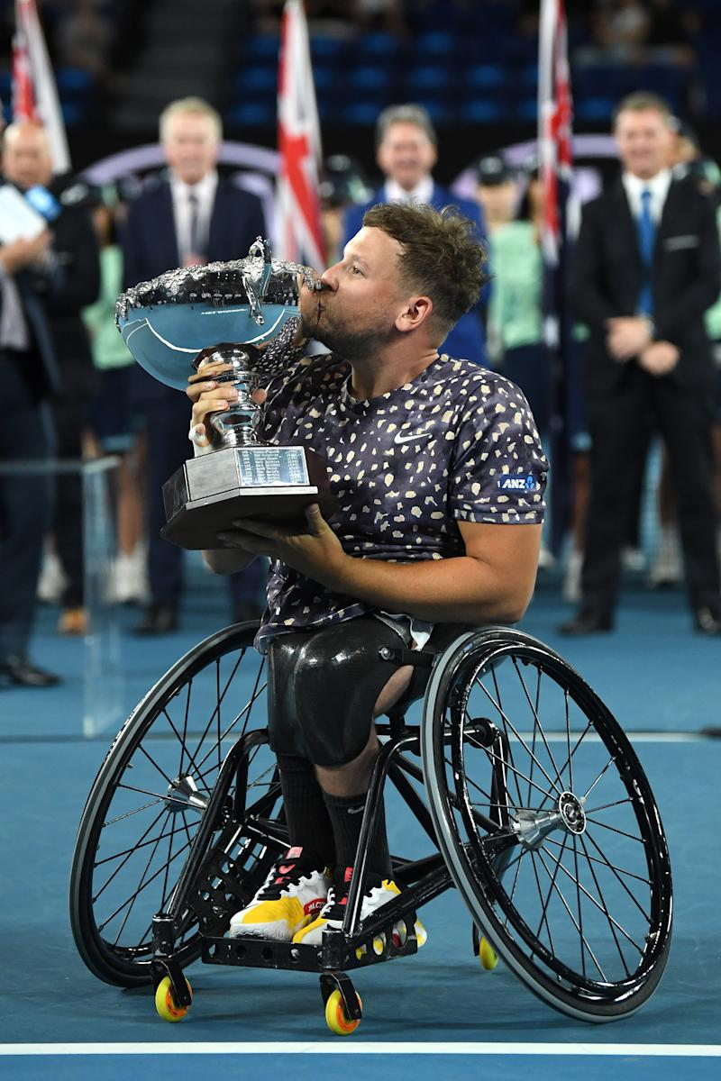 Dylan Alcott holds aloft the championship trophy.