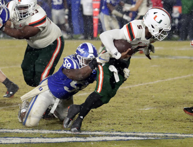 Miami's N'Kosi Perry (5) evades a tackle attempt by Duke's Tre Hornbuckle (59) during the fourth quarter of an NCAA college football game in Durham, N.C., Saturday, Nov. 30, 2019. (AP Photo/Chris Seward)
