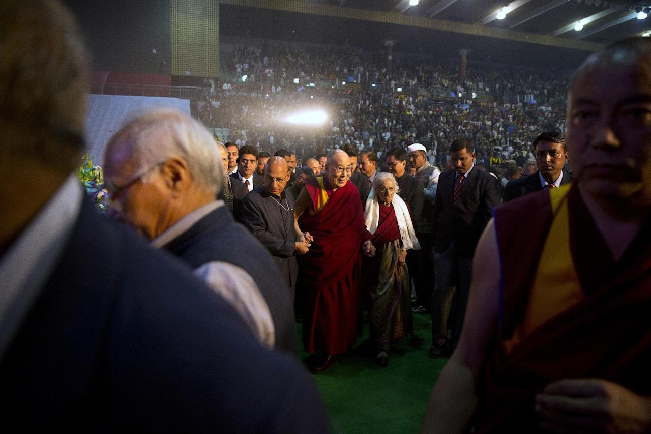 Tibetan spiritual leader, the Dalai Lama, center, leaves after at the inauguration of a four-day seminar on legacy of Tibet, Nalanda tradition of Buddhism, in New Delhi, India, Friday, Dec. 9, 2016. The four-day seminar will talk about Tibetan medicines and Buddhism. (AP Photo/Manish Swarup)