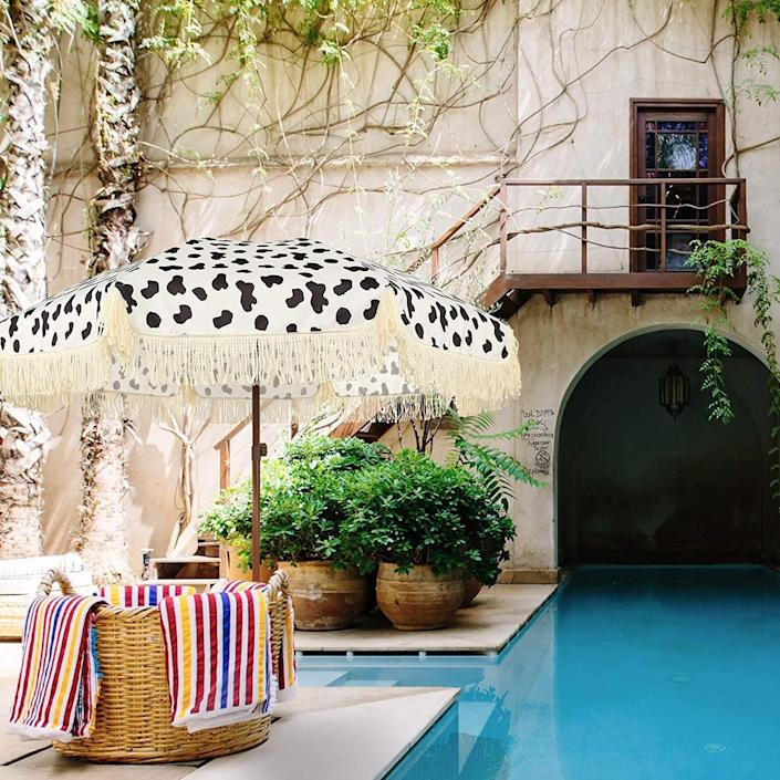 """Paired with a subtle <a href=""""https://www.architecturaldigest.com/gallery/decorating-with-animal-prints?mbid=synd_yahoo_rss"""" rel=""""nofollow noopener"""" target=""""_blank"""" data-ylk=""""slk:cow-print"""" class=""""link rapid-noclick-resp"""">cow-print</a> pattern, its ivory fringe is equally eye-catching. With a faux-wood steel pole and push-button tilt, the umbrella's carry bag allows easy transport to the beach or park. $81, Amazon. <a href=""""https://www.amazon.com/AMMSUN-Umbrella-Fringe-Outdoor-Tassel/dp/B0913K7T2T/"""" rel=""""nofollow noopener"""" target=""""_blank"""" data-ylk=""""slk:Get it now!"""" class=""""link rapid-noclick-resp"""">Get it now!</a>"""