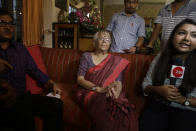 Nirmala Banerjee, mother of Abhijit Banerjee, center, interacts with media after Nobel Prize in economics was announced at her home in Kolkata, India, Monday, Oct. 14, 2019. The 2019 Nobel Prize in economics was awarded Monday to Abhijit Banerjee, Esther Duflo and Michael Kremer for pioneering new ways to alleviate global poverty. (AP Photo/Bikas Das)