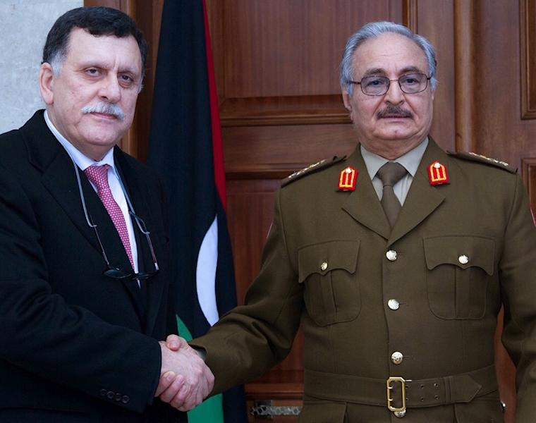 General Khalifa Haftar (R), commander of the armed forces loyal to the internationally recognised Libyan government, shakes hands with the head of the UN backed Libyan Presidential Council, Fayez al-Sarraj, in 2016 (AFP Photo/)