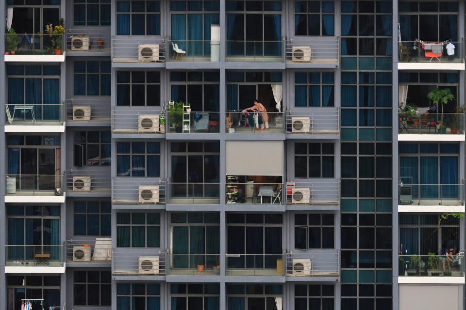 A woman hangs her clothes at the balcony apartment on August 30, 2021 in Singapore. (Photo by Suhaimi Abdullah/NurPhoto via Getty Images)