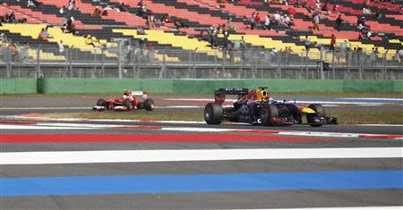 Red Bull Formula One driver Sebastian Vettel of Germany (R) races ahead of Ferrari Formula One driver Felipe Massa of Brazil in front of near empty stands during the third practice session of the Korean F1 Grand Prix at the Korea International Circuit in Yeongam, October 5, 2013. REUTERS/Kim Hong-Ji (