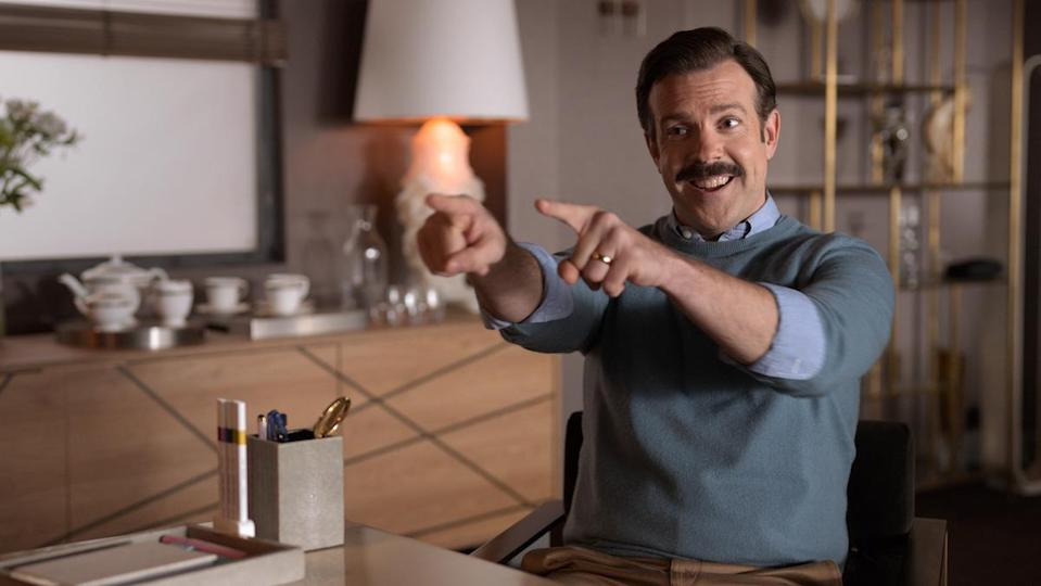 Ted Lasso (Jason Sudeikis) points while looking excited.