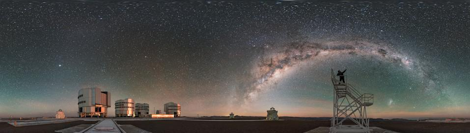 Under a sea of stars, a skywatcher points to the beautiful arch of the Milky Way Galaxy in this 360-degree panorama from the Paranal Observatory in Chile. The stargazer in this shot is European Southern Observatory (ESO) photo ambassador Babak Tafreshi, and on the left are the telescopes that make up ESO's Very Large Telescope array, which consists of four boxy Unit Telescopes and four smaller auxiliary telescopes. The image was recently featured as ESO's Picture of the Week.