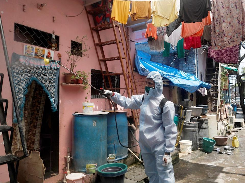A man wearing personal protective equipment (PPE) sprays disinfectant on the walls in an alley in a slum area in Mumbai, India, on June 29, 2020.