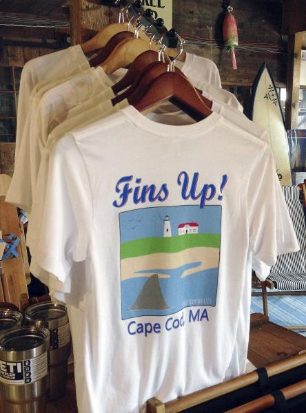 FILE - In this May 25, 2016 file photo, a shark-themed T-shirt is on sale at a souvenir shop in Harwich, Mass. Local chamber of commerce data suggests Cape Cod lodging and beach visit numbers are down in summer 2019, after uncommon tornados hit just one year after a pair of shark attacks. (AP Photo/Philip Marcelo, File)