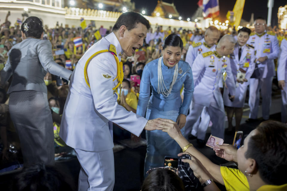 King Maha Vajiralongkorn, center left and and Princess Sirivannavari Nariratana, center right, greet supporters in Bangkok, Thailand, Sunday, Nov. 1, 2020. Under increasing pressure from protesters demanding reforms to the monarchy, Thailand's king and queen met Sunday with thousands of adoring supporters in Bangkok, mixing with citizens in the street after attending a religious ceremony inside the Grand Palace. (AP Photo/Wason Wanichakorn)