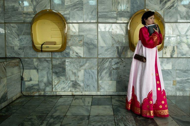 A North Korean woman in traditional dress uses a telephone inside the lobby of a hotel in Pyongyang on April 13, 2012. Cell phones were introduced into the country in 2008 through a joint venture with the Egyptian telecom firm Orascom, a domestic intranet was launched in 2002 and some state bodies have their own websites