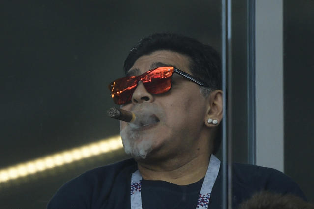 <p>Argentina legend Diego Maradona watches on with a cigar </p>