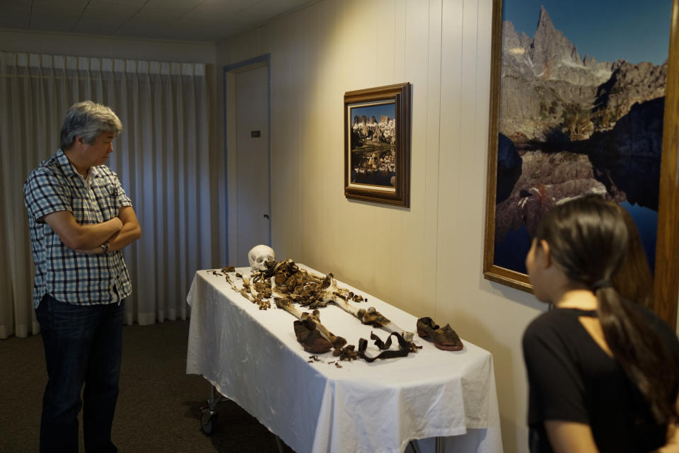 Wayne Matsumura, left, and his niece, Lilah Matsumura, look at the bones of their ancestor, Giichi Matsumura, at Brune Mortuary in Bishop, Calif., Monday, Feb. 17, 2020. Giichi Matsumura was a prisoner at the Manzanar internment camp during World War II and died on a hike in the Sierra in the waning days of the war in August 1945. Hikers discovered his mountainside grave and unearthed the skeleton in 2019, leading authorities to retrieve the bones and return them to the Matsumura family. (AP Photo/Brian Melley)