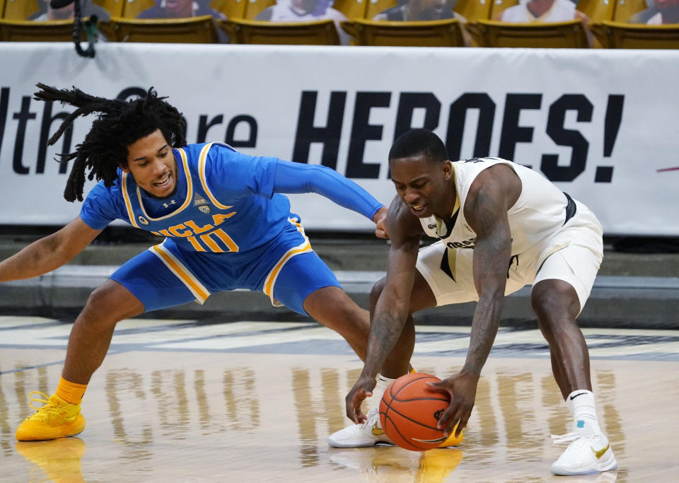 Colorado guard McKinley Wright IV, right, recovers the ball as UCLA guard Tyger Campbell defends in the first half of an NCAA college basketball game Saturday, Feb. 27, 2021, in Boulder, Colo. (AP Photo/David Zalubowski)