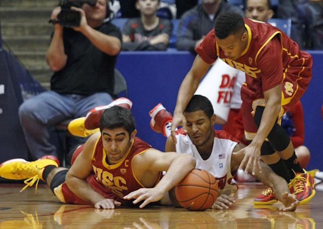 Southern California's Omar Oraby, left, and Chass Bryan, right, battle for the loose ball with Dayton's Jordan Sibert, center, during the first half of an NCAA college basketball game, Sunday, Dec. 22, 2013, in Dayton, Ohio. (AP Photo/Skip Peterson)
