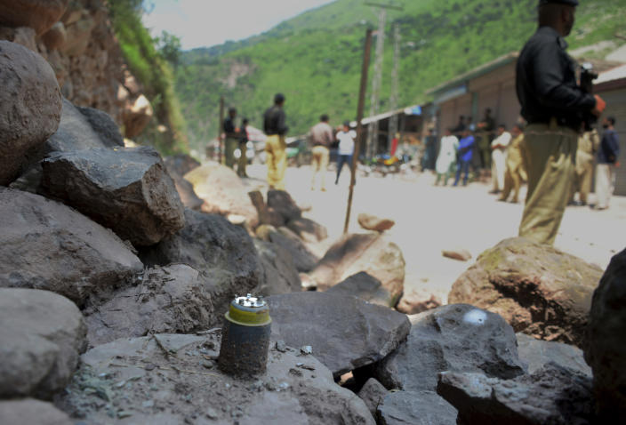 Police officers stand guard next to a munition fired by Indian forces on Nosehri village on the Line of Control that divides Kashmir between Pakistan India, near Muzaffarabad, Pakistan, Sunday, Aug. 4, 2019. Tensions have soared along the volatile, highly militarized frontier between India and Pakistan in the disputed Himalayan region of Kashmir, as India deployed more troops and ordered thousands of visitors out of the region. (AP Photo/M.D. Mughal)