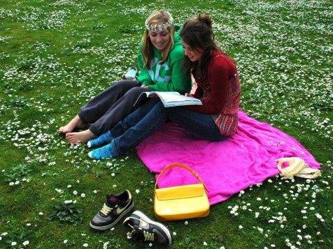 girls teens friends on grass in a park reading a book