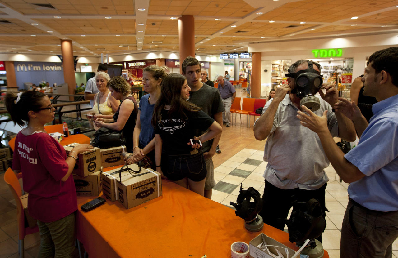 Israeli Aviv Levy tries on a gas mask as others wait in line, at a distribution center in a shopping mall in Mevaseret Zion near Jerusalem, Wednesday, July 25, 2012. Israel's foreign minister warned on Wednesday his country will act immediately if it discovers Islamic militants are raiding Syria's chemical or biological weapons stocks, while Israelis rushed to stock up on gas masks as the bellicose rhetoric swells. (AP Photo/Sebastian Scheiner)