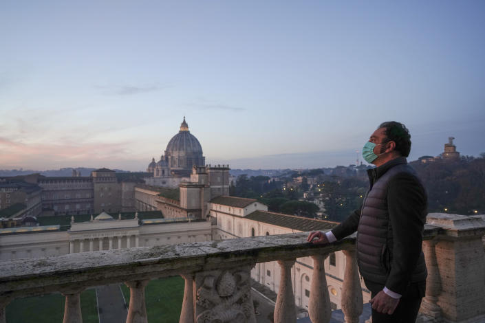 """Gianni Crea, the Vatican Museums chief """"Clavigero"""" key-keeper, poses for a photo on the """"Nicchione"""" terrace on his way to open the museum's rooms and sections, the Vatican, Monday, Feb. 1, 2021. Crea is the """"clavigero"""" of the Vatican Museums, the chief key-keeper whose job begins each morning at 5 a.m., opening the doors and turning on the lights through 7 kilometers of one of the world's greatest collections of art and antiquities. The Associated Press followed Crea on his rounds the first day the museum reopened to the public, joining him in the underground """"bunker"""" where the 2,797 keys to the Vatican treasures are kept in wall safes overnight. (AP Photo/Andrew Medichini)"""
