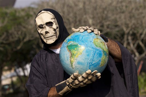 A man representing death holds a globe during a protest outside the People's Summit for Social and Environmental Justice in defense of the commons, a parallel event taking place alongside the United Nations Conference on Sustainable Development, or Rio 20, in Rio de Janeiro, Brazil, Friday, June 15, 2012. (AP Photo/Silvia Izquierdo)