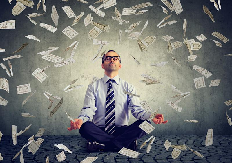 A man sitting in a yoga pose as $100 bills fall down around him.