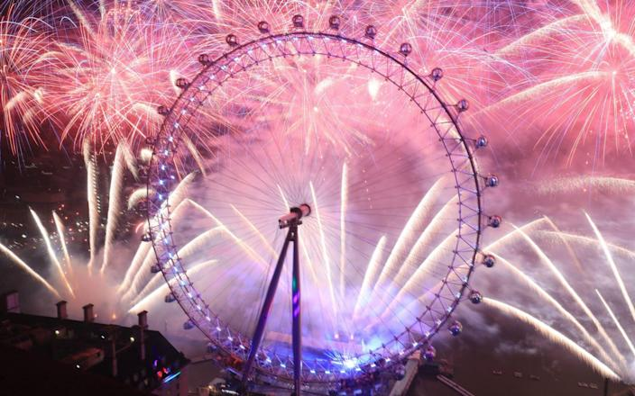 Fireworks light up the sky over the London Eye in central London during the New Year celebrations - PA