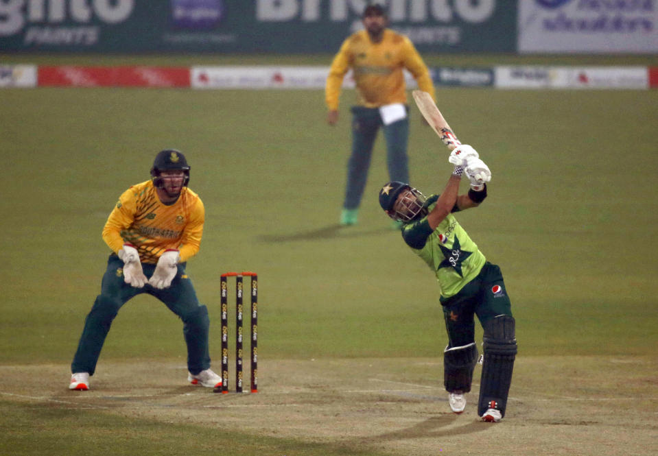 Pakistan's Mohammad Rizwan, right, plays a shot for six while South Africa's Heinrich Klaasen, left, watches during the 3rd Twenty20 cricket match between Pakistan and South Africa at the Gaddafi Stadium, in Lahore, Pakistan, Sunday, Feb. 14, 2021. (AP Photo/K.M. Chaudary)