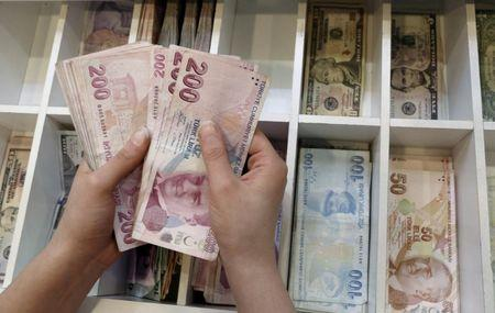 FILE PHOTO: A money changer counts Turkish lira bills at an currency exchange office in central Istanbul, Turkey