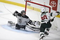 Los Angeles Kings goalie Jonathan Quick, left, stretches to block a shot by Minnesota Wild center Marcus Johansson during the first period of an NHL hockey game in Los Angeles, Saturday, Jan. 16, 2021. (AP Photo/Kelvin Kuo)