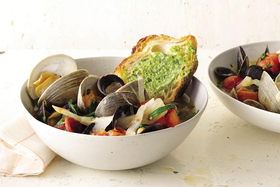 """Briny shellfish give this quick bouillabaisse its depth of flavor. Basil rouille (a garlicky Provençal mayonnaise) adds vibrancy. <a href=""""https://www.epicurious.com/recipes/food/views/summer-tomato-bouillabaisse-with-basil-rouille-366433?mbid=synd_yahoo_rss"""" rel=""""nofollow noopener"""" target=""""_blank"""" data-ylk=""""slk:See recipe."""" class=""""link rapid-noclick-resp"""">See recipe.</a>"""