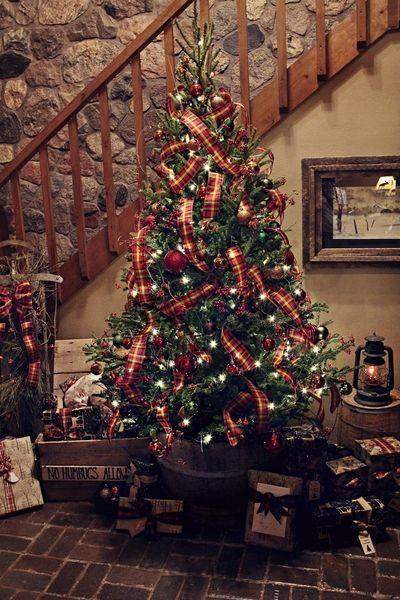 "<p>A country-style tree by <a href=""https://www.christopherhiedeman.com/"" rel=""nofollow noopener"" target=""_blank"" data-ylk=""slk:Christopher Hiedeman"" class=""link rapid-noclick-resp"">Christopher Hiedeman</a> is woven with warm red ribbons and decorative berries for a twist on tradition in this rustic home.</p>"