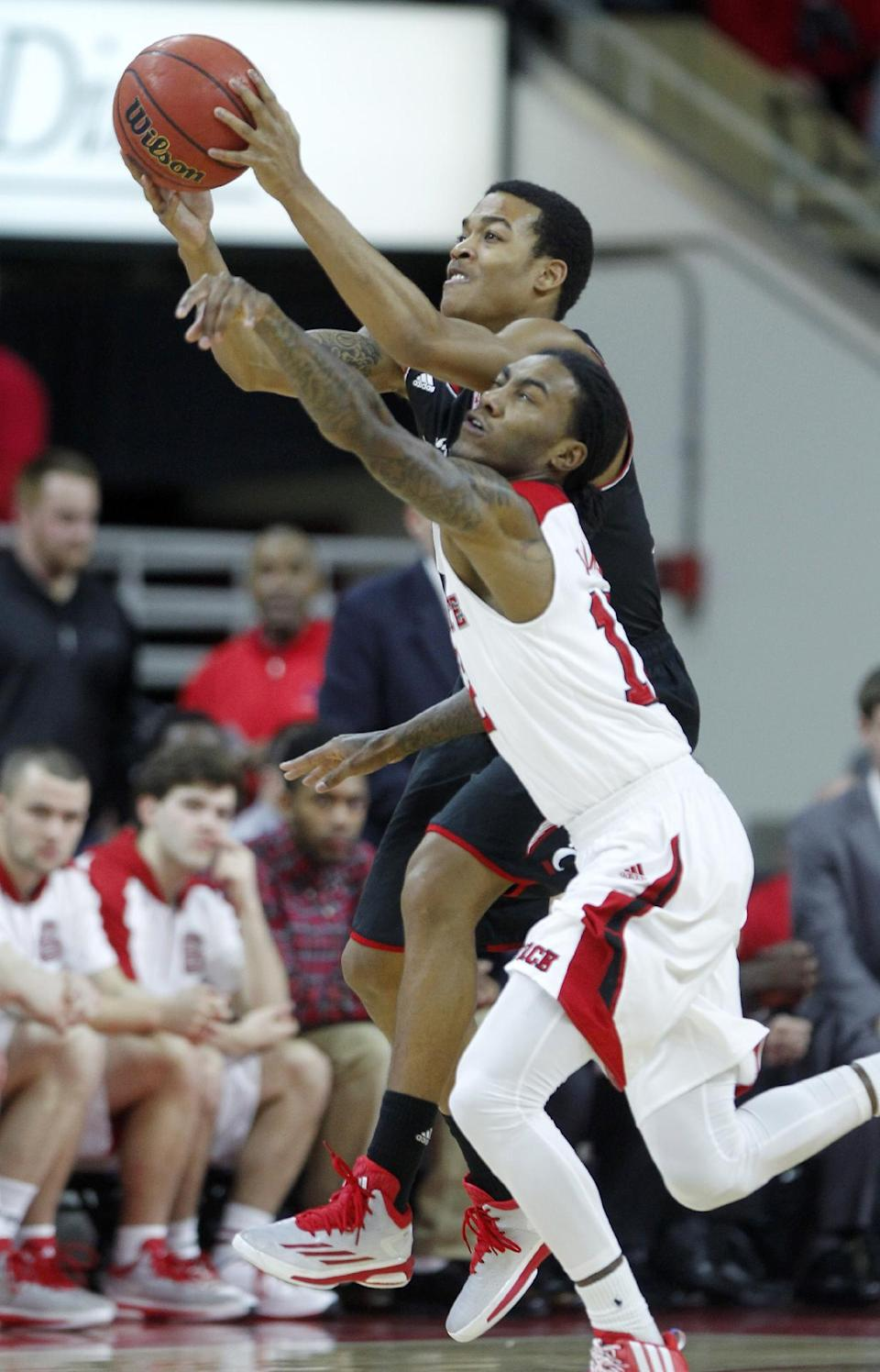 North Carolina State's Cat Barber, front, tries to steal the ball from Cincinnati's Troy Caupain (10) during the first half of an NCAA college basketball game Tuesday, Dec. 30, 2014, in Raleigh, N.C. (AP Photo/The News & Observer, Ethan Hyman)