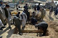 Shiite mourners and relatives dig graves for girls who died in multiple blasts outside a school in Kabul