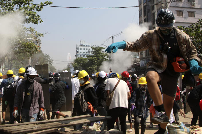 Protesters are dispersed as riot police fired tear gas behind a makeshift barricade in Yangon, Myanmar, Sunday, March 7, 2021. The escalation of violence in Myanmar as authorities crack down on protests against the Feb. 1 coup is raising pressure for more sanctions against the junta, even as countries struggle over how to best sway military leaders inured to global condemnation. (AP Photo)
