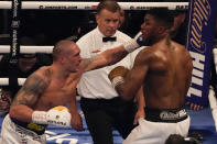 Oleksandr Usyk of Ukraine, left, throws a punch at Anthony Joshua of Britain during their WBA (Super), WBO and IBF boxing title bout at the Tottenham Hotspur Stadium in London, Saturday, Sept. 25, 2021. (AP Photo/Frank Augstein)