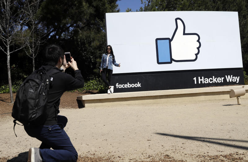 Visitors take photos in front of the Facebook logo at the company's headquarters Wednesday, March 28, 2018, in Menlo Park , Calif. (AP Photo/Marcio Jose Sanchez)