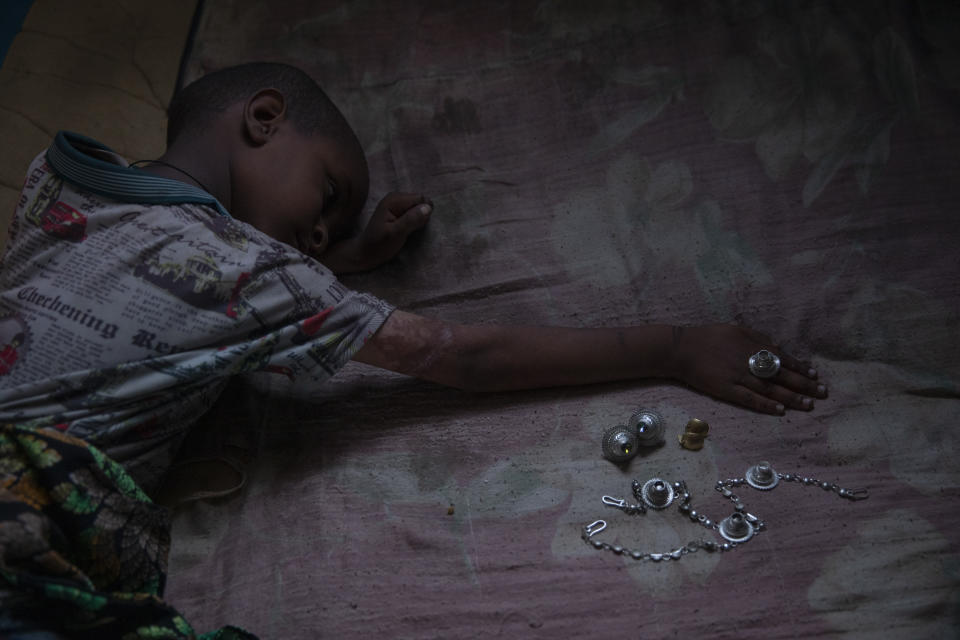 Tigrayan 5-year-old refugee Micheale Gebremariam plays with jewelry belonging to his deceased mother, Letay, inside the family's shelter in Hamdayet, eastern Sudan, near the border with Ethiopia, on March 14, 2021. (AP Photo/Nariman El-Mofty)