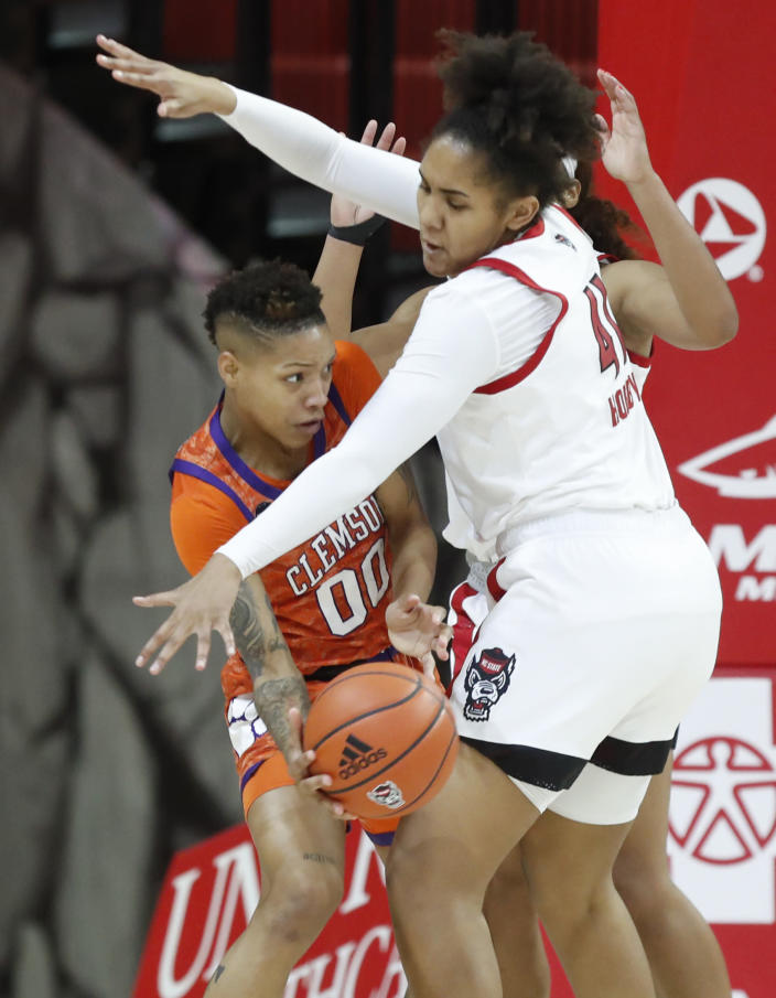 Clemson's Delicia Washington (00) passes around the pressure by North Carolina State's Camille Hobby (41) during the first half of an NCAA college basketball game at Reynolds Coliseum in Raleigh, N.C., Thursday, Feb. 11, 2021. (Ethan Hyman/The News & Observer via AP)