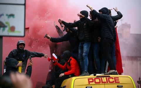 Fans stand on top of a police van amid smoke from flares outside the stadium before the Champions League semi-final - Credit: Dave Thompson/AP