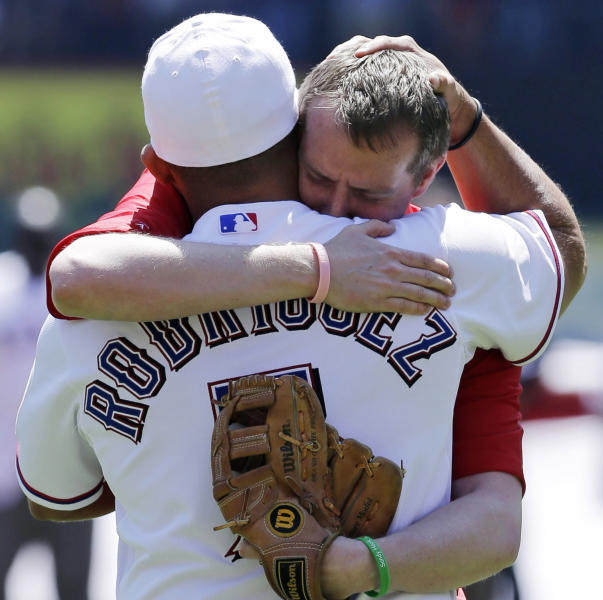 Robbie Parker, right, receives a hug from Texas Rangers representative Ivan Rodriguez after throwing out the ceremonial first pitch before a baseball game between the Los Angeles Angels and the Rangers, Friday April 5, 2013, in Arlington, Texas. Parker, a North Texas native whose 6-year-old daughter, Emilie, was among the victims of the Sandy Hook school shooting in Connecticut, threw out the first pitch before the Rangers' home-opener, their favorite team. (AP Photo/Tony Gutierrez)