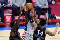 Washington Wizards' Bradley Beal, center, goes up for a shot against Philadelphia 76ers' Danny Green, right, and Joel Embiid during the second half of Game 2 in a first-round NBA basketball playoff series, Wednesday, May 26, 2021, in Philadelphia. (AP Photo/Matt Slocum)
