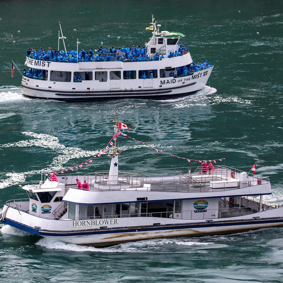 American tourist boat glides past a Canadian vessel limited to just six passengers in Niagara Falls (Carlos Osorio / Reuters)