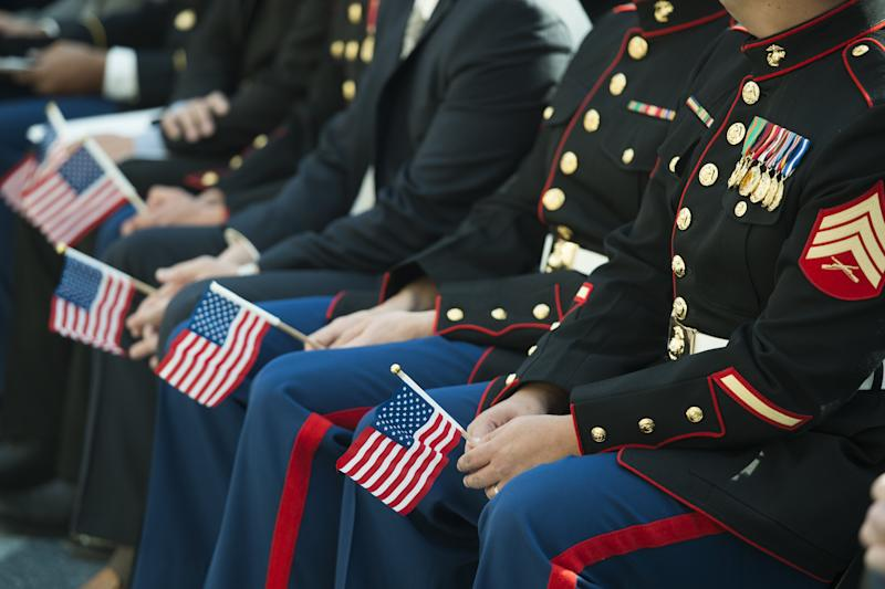 Twenty-six individuals from around the world, including active members of the US military, military veterans and military spouses, hold American flags prior to taking the oath to become US citizens in Triangle, Virginia, November 10, 2014 (AFP Photo/Saul Loeb)