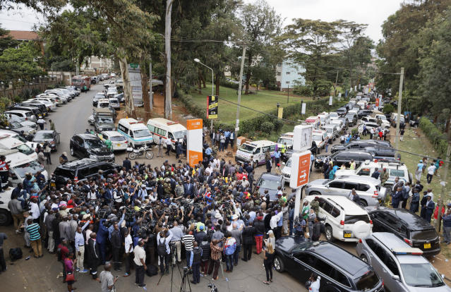 Media surround Kenya's Interior Minister Fred Matiang'i as he gives a statement at the scene of the attack Wednesday, Jan. 16, 2019 in Nairobi, Kenya. Extremists stormed a luxury hotel in Kenya's capital on Tuesday, setting off thunderous explosions and gunning down people at cafe tables in an attack claimed by Africa's deadliest Islamic militant group. (AP Photo/Ben Curtis)