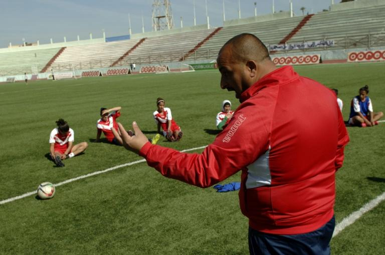 Coach Sid Ahmed Mouaz (R) instructs his players during a training session in the Algerian city of Relizane
