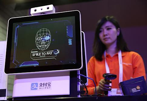 "An Alibaba employee demonstrates ""Smile to Pay"", an automatic facial recognition payment system at the Alibaba booth at the CES expo in Las Vegas in January 2017. Photo: Getty Images via AFP"
