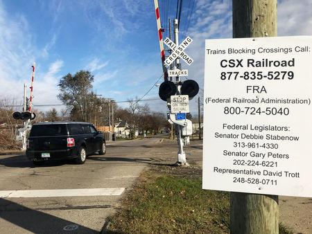 FILE PHOTO: A sign at a rail crossing tells motorists how to file a complaint about delays caused by long CSX trains  near Detroit, Michigan November 27, 2017.  REUTERS/Joe White/File Photo