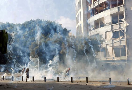 Demonstrators run to take cover from tear gas fired by police during a protest (REUTERS)